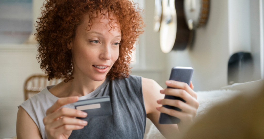 Women looking at phone holding credit card
